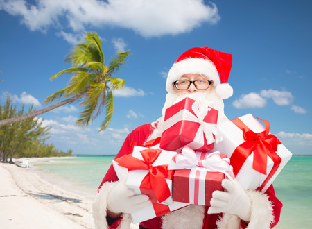 christmas, holidays and people concept - man in costume of santa claus with gift boxes over tropical beach background photo