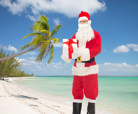 christmas, holidays, travel and people concept - man in costume of santa claus with gift box over tropical beach background photo