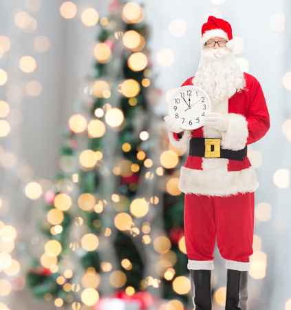 twelve month old: christmas, holidays and people concept - man in costume of santa claus with clock showing twelve over tree lights  Stock Photo