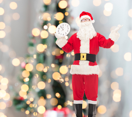 christmas, holidays and people concept - man in costume of santa claus with clock showing twelve over tree lights  Stock Photo