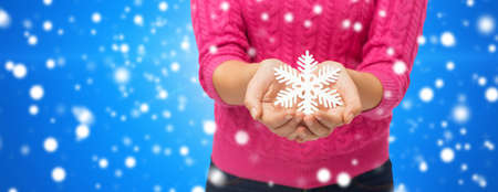 christmas, winter, holidays and people concept - close up of woman in pink sweater holding snowflake decoration over blue snowy  photo