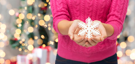 christmas, holidays and people concept - close up of woman in pink sweater holding snowflake decoration over tree lights  photo