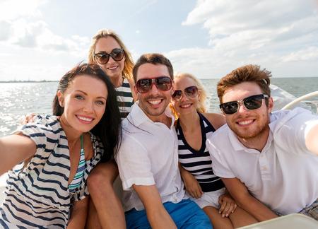 休暇、旅行、海、友情および人々 のコンセプト - ヨットのデッキの上に座って、selfie を作ると友達に笑顔 写真素材