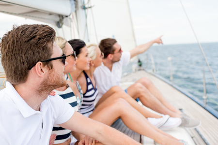 boat party: vacation, travel, sea, friendship and people concept - smiling friends sitting on yacht deck and pointing finger
