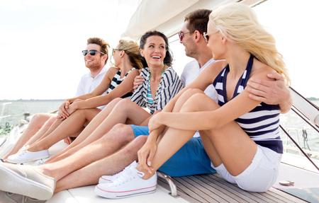 fiesta familiar: vacaciones, viaje, mar, la amistad y la gente conceptuales - sonriendo amigos sentados en la cubierta del yate Foto de archivo