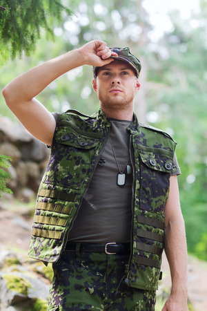 infantryman: war, army and people concept - young soldier or ranger wearing military uniform in forest Stock Photo