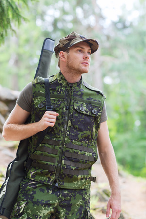 hunting, war, army and people concept - young soldier, ranger or hunter with gun walking in forest photo