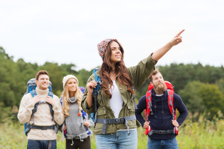 adventure holiday: adventure, travel, tourism, hike and people concept - group of smiling friends with backpacks pointing finger outdoors Stock Photo