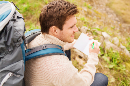 people travelling: adventure, travel, tourism, hike and people concept - smiling man with backpack sitting on ground