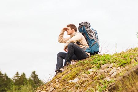 lejos: aventura, viajes, turismo, ir de excursión y la gente concepto - el hombre con mochila sentado en el suelo y mirando a lo lejos