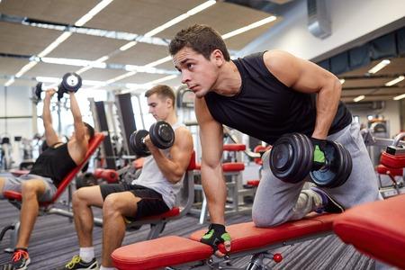 фитнес: спорт, фитнес, образ жизни и люди концепции - группа людей, изгибать мышцы с гантелями в тренажерном зале