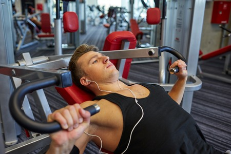 working out: sport, equipment, technology, lifestyle and people concept - young man with earphones flexing chest muscles on gym machine
