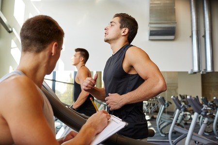 personal: sport, fitness, lifestyle, technology and people concept - men with personal trainer exercising on treadmill in gym