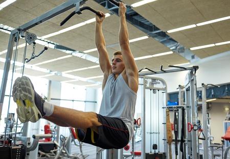 fitness men: deporte, fitness, estilo de vida y las personas concepto - joven flexionando los m�sculos abdominales en la barra de pull-up en el gimnasio