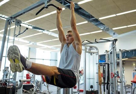to raise: sport, fitness, lifestyle and people concept - young man flexing abdominal muscles on pull-up bar in gym