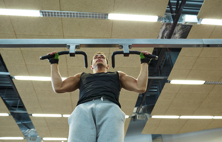 pullups: sport, fitness, lifestyle and people concept - young man doing pull-ups in gym