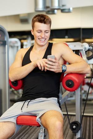 hombre fuerte: deporte, culturismo, estilo de vida, la tecnolog�a y la gente concepto - hombre joven sonriente con el tel�fono inteligente en el gimnasio Foto de archivo
