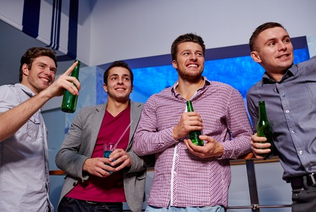 leisure time: nightlife, party, friendship, leisure and people concept - group of smiling male friends with beer bottles drinking in nightclub