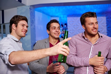 chilling out: nightlife, party, friendship, leisure and people concept - group of smiling male friends with beer bottles drinking in nightclub
