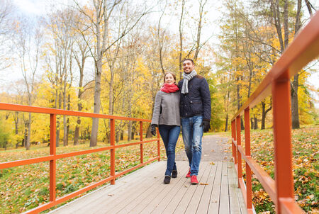 love, relationship, family, season and people concept - smiling couple hugging on bridge in autumn park photo