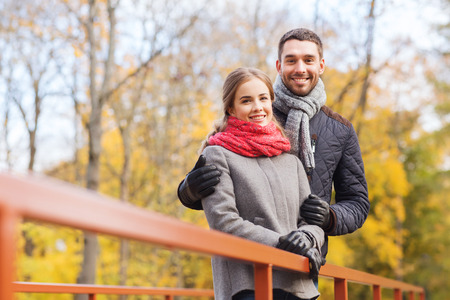 lovers park: love, relationship, family, season and people concept - smiling couple hugging on bridge in autumn park