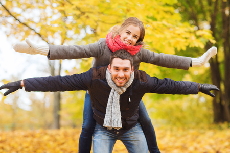 autumn in the park: love, relationship, family and people concept - smiling couple having fun in autumn park Stock Photo