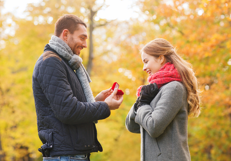 love, family, autumn and people concept - smiling couple with engagement ring in small red gift box outdoors photo