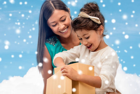 christmas, holidays, family and people concept - happy mother and child girl with gift box over blue snowy sky with cloud background photo