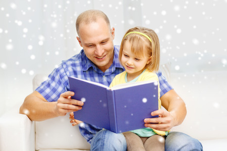 family, children, education and happy people concept - smiling father and daughter reading book at home photo