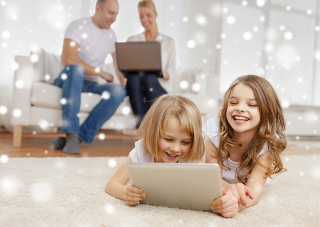 family, home, technology and people - smiling mother, father and little girls with tablet pc computer over snowflakes  photo