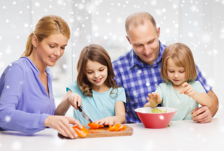 food, family, children, happiness and people concept - happy family with two kids making dinner at home photo