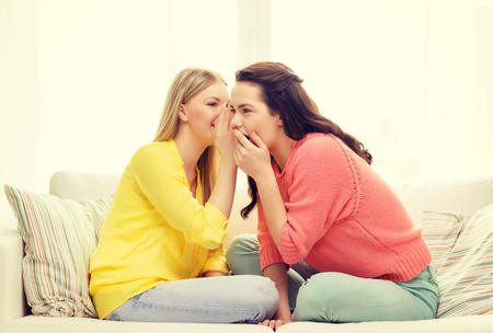 girl bonding: friendship, gossip and happiness concept - one girl telling another secret Stock Photo