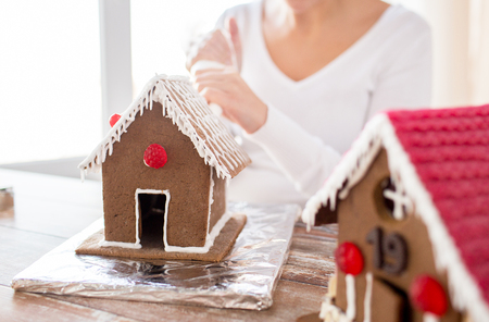 cooking, people, christmas and decoration concept - happy woman making gingerbread houses at home photo