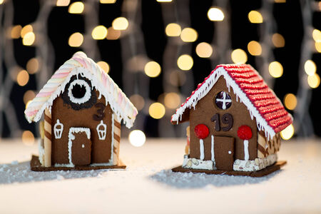sugarcoated: holidays, christmas, baking and sweets concept - closeup of beautiful gingerbread houses on table over black garland lights