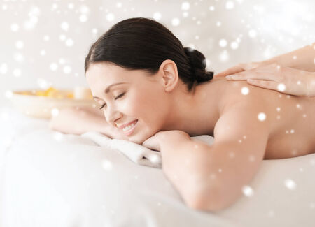 body massage: beauty, health, holidays, people and spa concept - beautiful young woman in spa salon getting massage