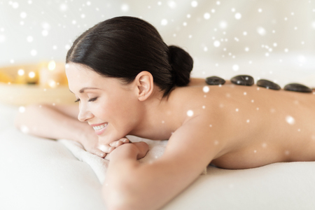 beauty, health, people and spa concept - beautiful woman in\ spa salon getting hot stones massage