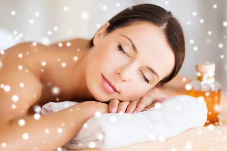 body oil: beauty, health, people and spa concept - beautiful young woman with body oil in spa Stock Photo