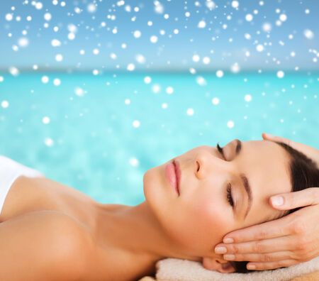 head massage: beauty, health, holidays, people and spa concept - beautiful woman in spa salon getting face or head massage over sky and sea with snowflakes background Stock Photo