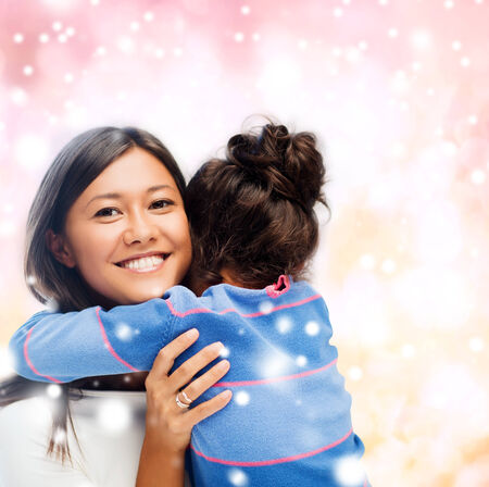 asian preteen: childhood, happiness, family and people concept - smiling little girl and mother hugging over pink snowy background Stock Photo
