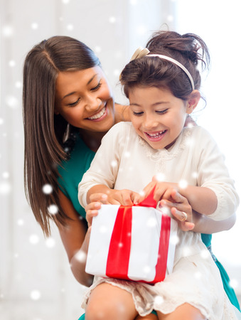 asian family home: holidays, presents, christmas, x-mas concept - happy mother and child girl with gift box over snowy background
