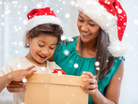 latino family: christmas, holidays, family and people concept - happy mother and child girl with gift box at home