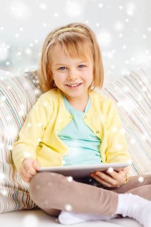 hollidays: childhood, toys, technology and happiness concept - smiling little girl with tablet pc computer sitting on sofa at home