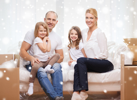 accommodation: family, people, accommodation and happiness concept - smiling parents and two little girls moving into new home over snowflakes background Stock Photo