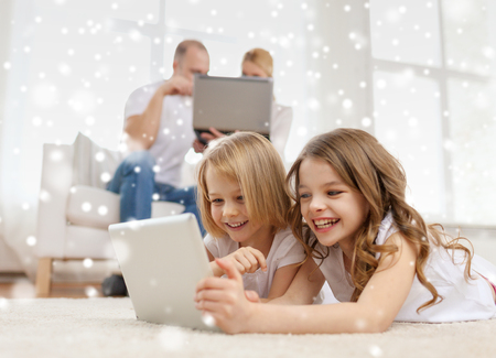 family, home, technology and people - smiling mother, father and little girls with tablet pc computer over snowflakes background photo