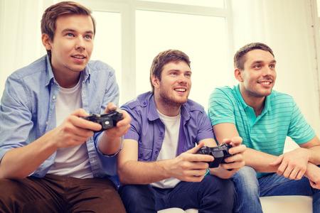 jugando videojuegos: amistad, tecnología, juegos y concepto de hogar - sonrientes amigos varones jugando juegos de video en casa