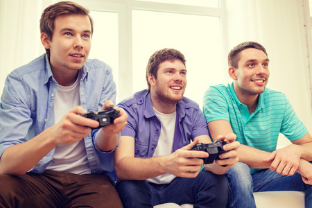 gamer: friendship, technology, games and home concept - smiling male friends playing video games at home