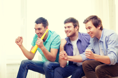 vuvuzela: friendship, sports and entertainment - happy male friends with vuvuzela watching sports at home Stock Photo