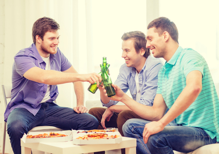 friendship, food and leisure concept - smiling male friends with beer and pizza hanging out at home photo