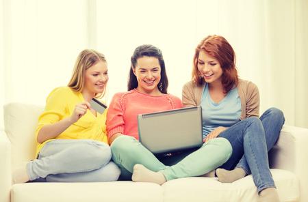 orden de compra: amistad, el dinero, la tecnología y la internet concepto - tres sonrientes chicas adolescentes con el ordenador portátil y una tarjeta de crédito en casa