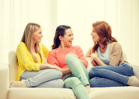 friendship and happiness concept - three girlfriends having a talk at home